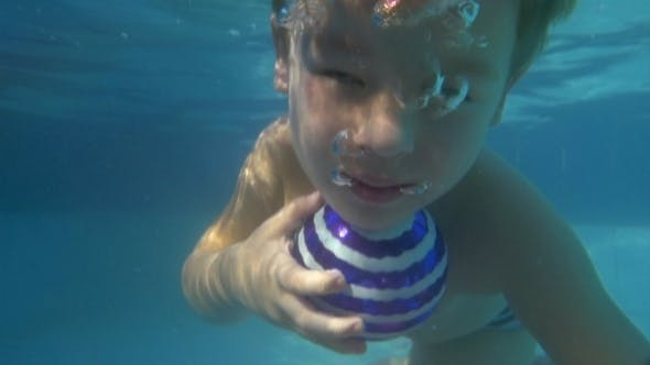 Cover Image for Child Diving With Ball In The Pool