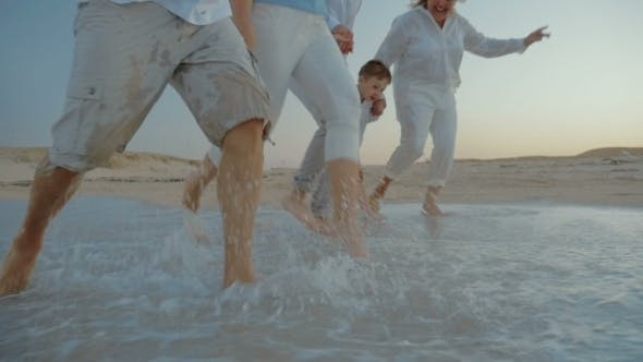 Thumbnail for Family Walking On The Beach And Splashing Water