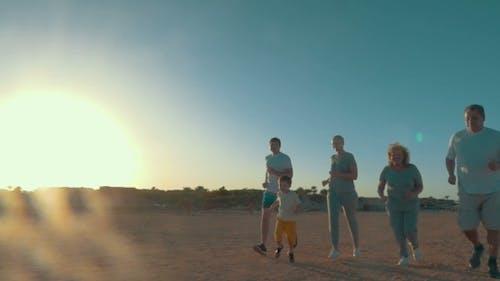 Family Run On The Beach At Sunset