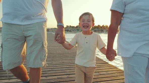 Thumbnail for Happy Boy Walking With Grandparents Along The Pier