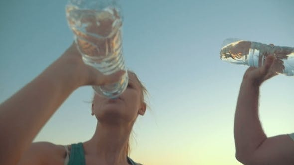 Thumbnail for Two People Drinking Water From Plastic Bottles