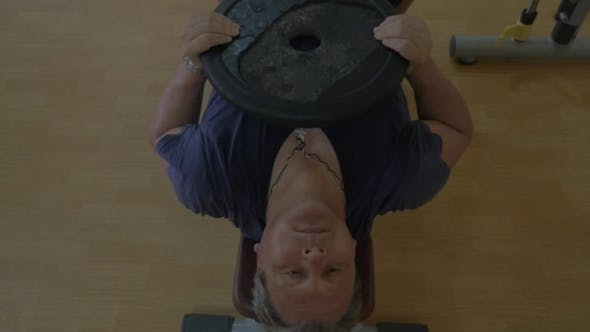 Thumbnail for Man Exercising With Weight Plate In The Gym