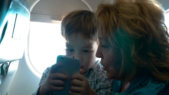 Thumbnail for Grandmother And Grandson With Cell In The Plane