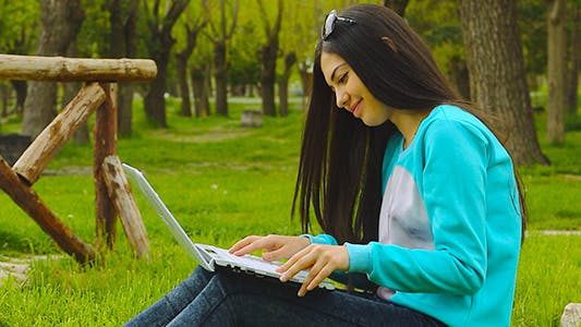 Thumbnail for Girl Using Laptop in Park
