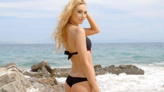 Cover Image for Frau in Bikini schauen über Schulter auf Strand