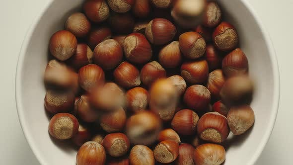 Thumbnail for Inshell hazelnuts falling into a white bowl