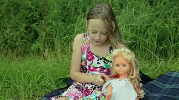 Thumbnail for Young Girl Playing With Doll On Outside Grass