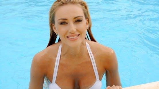Thumbnail for Lächelnde Frau in weiß Bikini aufstrebende am Pool