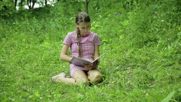 Thumbnail for Young Girl Reading Book In The Park