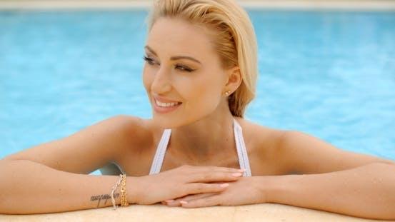 Thumbnail for ziemlich blond Frau lehnte bei die poolside