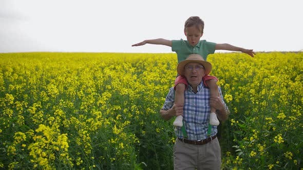 Grandfather and Grandson During Walk Through Field