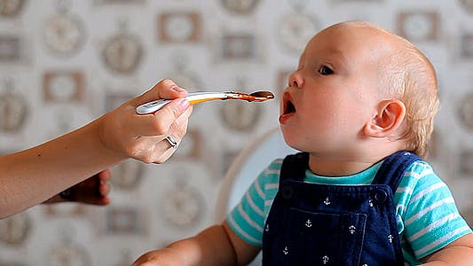 Mum Feeds the Child with a Spoon
