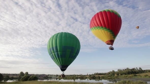Thumbnail for Hot Air Balloons Flying Over Lake And Field