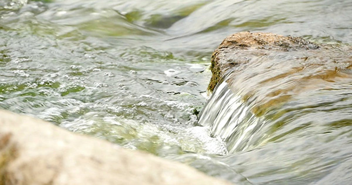 Fast Flowing River With Stones In The Water