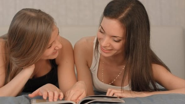 Thumbnail for Two Happy Girls Reading a Magazine On The Bed At