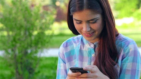 Cover Image for Beautiful Smiling Young Woman Using Mobile In Park