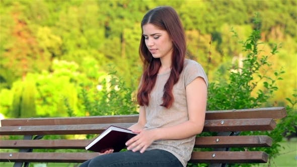 Thumbnail for Attractive Girl With a Diary Sitting On The Bench