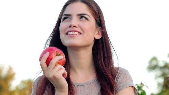Thumbnail for Portrait Of Smiling Beautiful Girl With An Apple