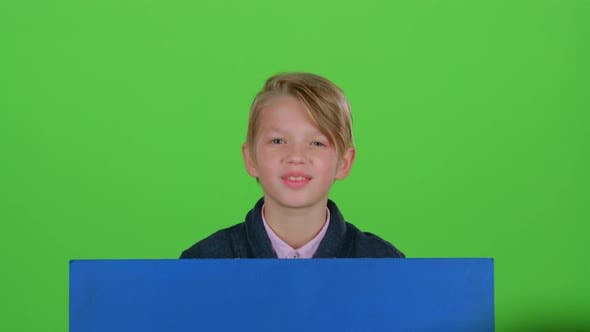 Thumbnail for Child Boy in Jumper Emerges From Behind the Board and Waving on a Green Screen