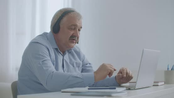 Middle-aged Man Is Talking By Video Chat with Colleagues, Working Remotely, Connecting with