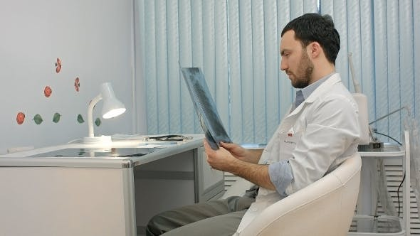 Thumbnail for Male Doctor Or Dentist Looking At X-ray