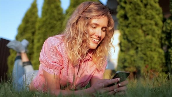 Thumbnail for Beautiful Girl Laying On Grass, Using Mobile Phone