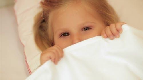 Niedlich kleines Mädchen unter die Decke