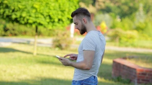Cover Image for Young Man Standing In The Park With Mobile Phone
