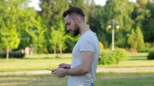 Thumbnail for Young Man Walking In The Park With Mobile Phone