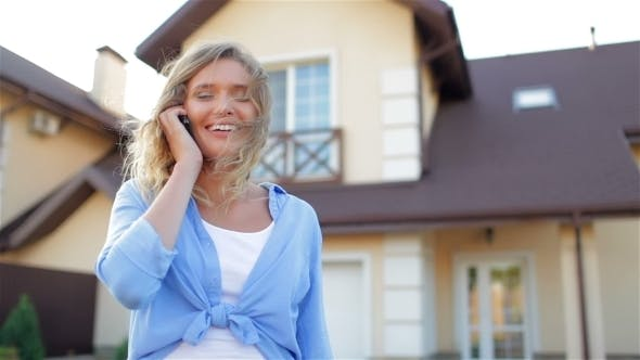 Thumbnail for Beautiful Girl Talking On Phone Next To New House