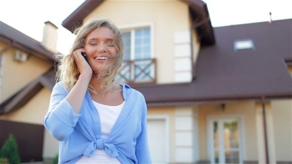Thumbnail for schön Mädchen reden auf Telefon neben neue Haus