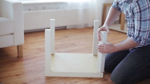 Thumbnail for Male Hands Assembling Legs To Table At Home
