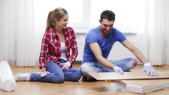Thumbnail for Happy Couple Measuring Wood Flooring Board At Home