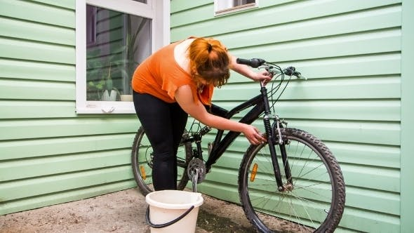 Thumbnail for Young Girl Washing The Bicycle Wheels