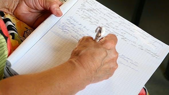 Thumbnail for Frau schreibt einen Stift in einem Notizbuch