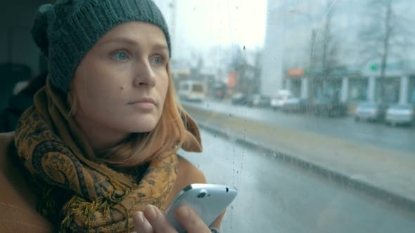 Thumbnail for Woman Using Phone In Bus On Rainy Day