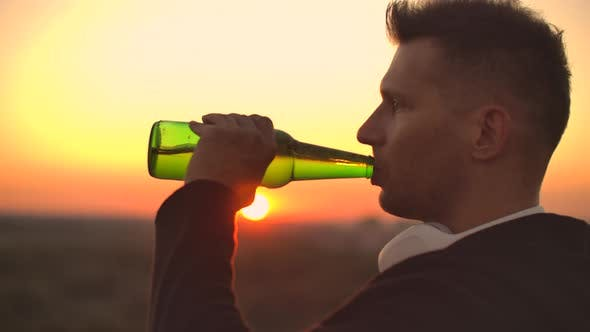 Thumbnail for Close Up of a Man Drinking Beer at Sunset Standing on the Roof of a Building Against the Background