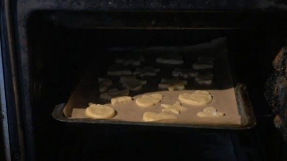 Backblech mit Plätzchen in den Ofen legen