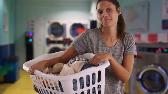 Thumbnail for Smiling young woman holding basket of clothes in laundry room
