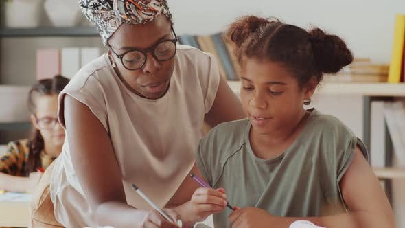Thumbnail for Afro-American Female Teacher Helping Girl during Lesson in Elementary School