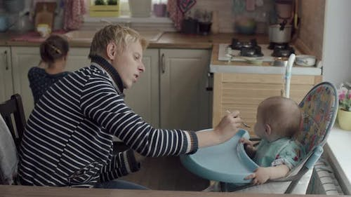 Young Father Feeding His Kid From A Spoon In The Kitchen At Home