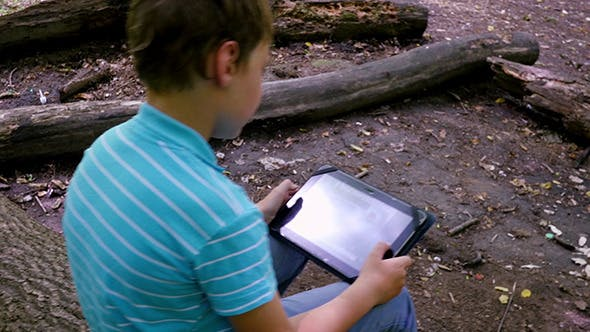Thumbnail for Boy With Tablet In The Forest