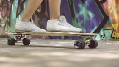Feet Of a Man In Sneakers On Top Of Longboard