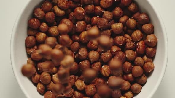 Thumbnail for Hazelnuts Falling Into A White Bowl