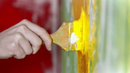Painting Wall with Yellow Color Paint Using a Brush - Interior Design