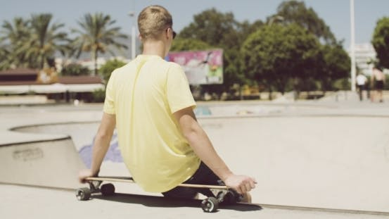 Thumbnail for Teenager Is Sitting On His Longboard