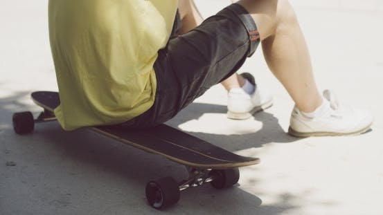 Thumbnail for Boy Sitting On a Skateboard Outdoors