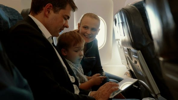 Thumbnail for Family Of Three In Plane With Smartphone