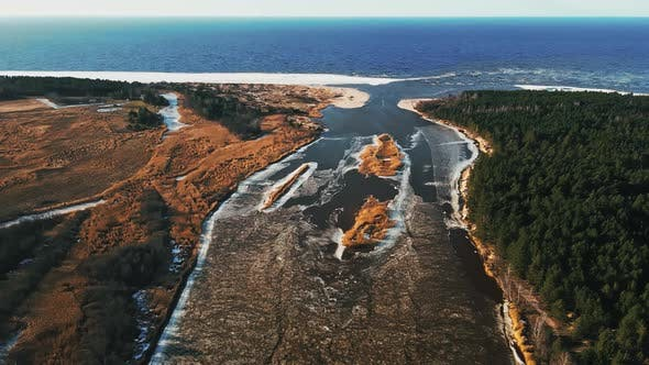 High Angle Melting Snow and Ice at River Joining Sea in Spring Aerial