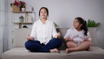 Mother teaching her daughter to meditate on the sofa